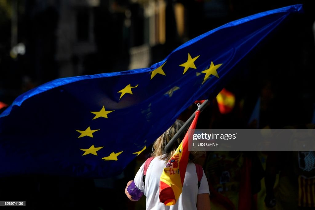 A protesters holds an European flag during a demonstration called by 'Societat Civil Catalana' (Catalan Civil Society) to support the unity of Spain on October 8, 2017 in Barcelona. Ten of thousands of flag-waving demonstrators packed central Barcelona to rally against plans by separatist leaders to declare Catalonia independent following a banned secession referendum. Catalans calling themselves a 'silent majority' opposed to leaving Spain broke their silence after a week of mounting anxiety over the country's worst political crisis in a generation. GENE
