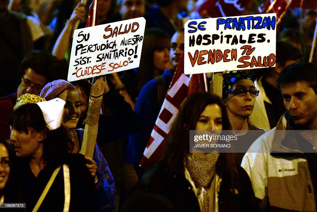 Protesters holds placards reading 'Their welfare harms our healthcare system! 'Take care of yourself' (L) and 'They privatize hospitals. They sell your health' as they attend a demonstration during a general strike on November 14, 2012 in Madrid. The second general strike this year hit Spain with protesters marching in several cities against sweeping austerity measures and high unemployment, scenes echoed elsewhere in Europe. Spain, the eurozone's fourth-biggest economy, is suffering 25 percent unemployment, with the rate even higher amongst young people.