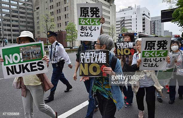 Protesters holds placards to criticize Japanese Prime Minister Shinzo Abe and the government's nuclear energy policy during a demonstration march in...