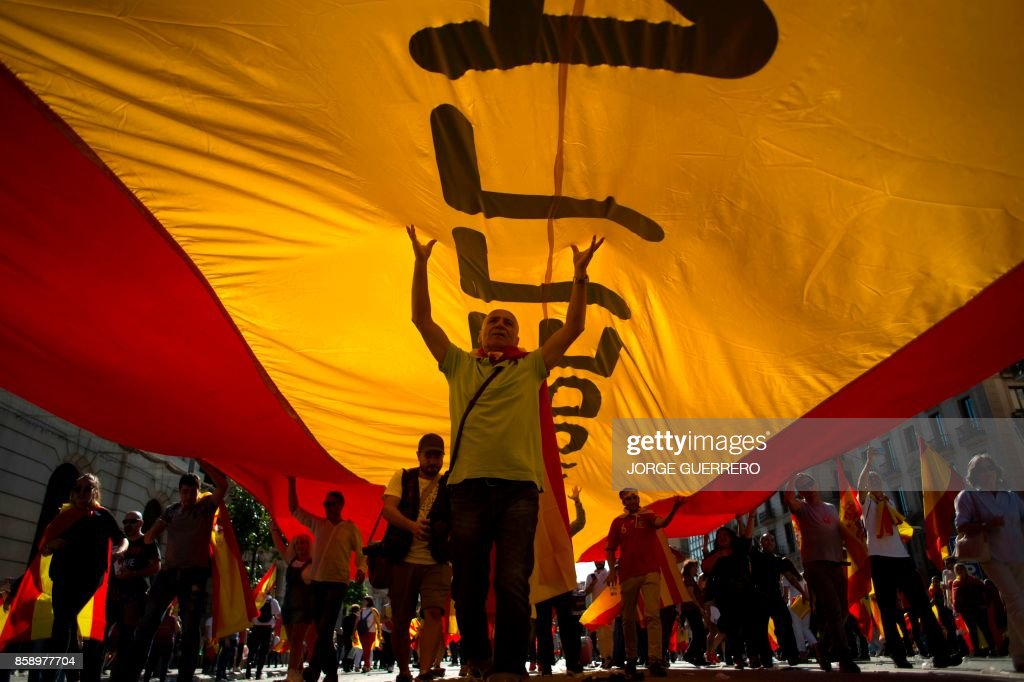 TOPSHOT - Protesters hols a giant Spanish flag during a demonstration called by 'Societat Civil Catalana' (Catalan Civil Society) to support the unity of Spain on October 8, 2017 in Barcelona. Ten of thousands of flag-waving demonstrators packed central Barcelona to rally against plans by separatist leaders to declare Catalonia independent following a banned secession referendum. Catalans calling themselves a 'silent majority' opposed to leaving Spain broke their silence after a week of mounting anxiety over the country's worst political crisis in a generation. GUERRERO