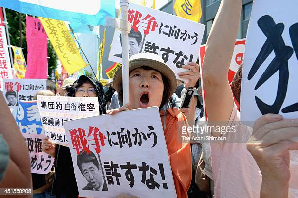 Protesters in front of the prime minister's office shout their opposition to the Abe Cabinet's move to allow Japan to exercise the right to...