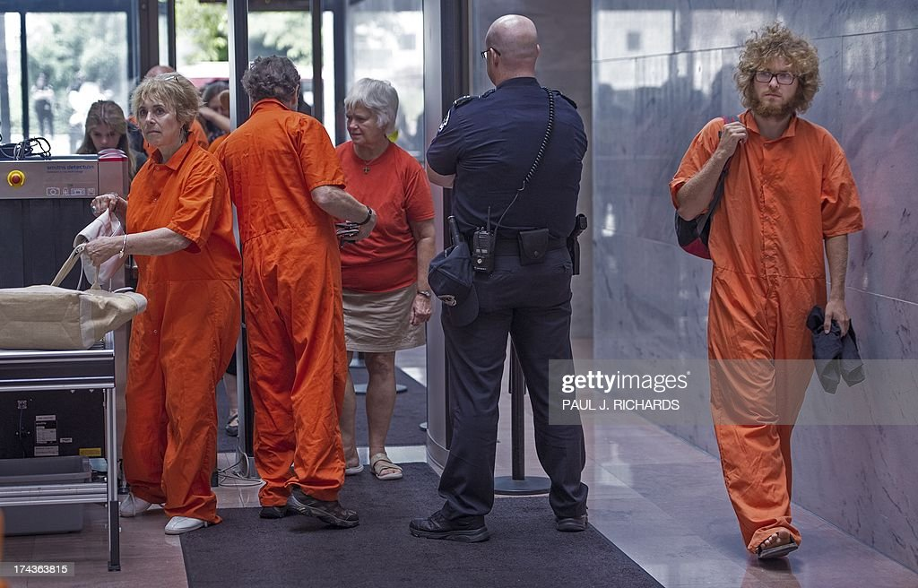 Protesters in support of closing the US Guantanmo Naval Base detention facility enter the Hart Senate Office Building going thru a security check point with a US Capitol Police Officer watching them closely in their orange jump suits on their way a to attend the Senate Judiciary Committee, The Constitution, Civil Rights and Human Rights Subcommittee hearing on 'Closing Guantanamo: The National Security, Fiscal, and Human Rights Implications.', July 24, 2013, on Capitol Hill in Washington, DC. AFP PHOTO/Paul J. Richards
