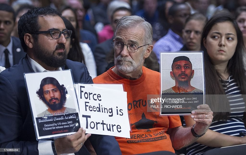 Protesters in support of closing the US Guantanmo Naval Base detention facility hold signs and photos of detainees as they listen in the public audience area of the Senate Judiciary Committee, The Constitution, Civil Rights and Human Rights Subcommittee hearing on 'Closing Guantanamo: The National Security, Fiscal, and Human Rights Implications.', July 24, 2013, on Capitol Hill in Washington, DC. AFP PHOTO/Paul J. Richards