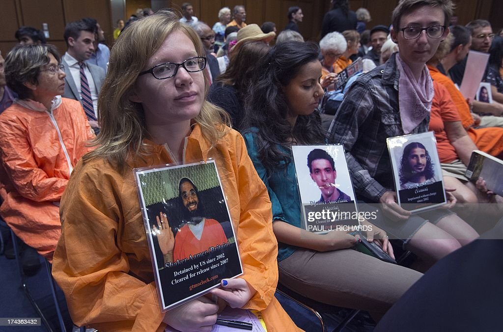 Protesters in support of closing the US Guantanmo Naval Base detention facility wear orange jumpsuits and hold photos of detainees as they listen in the public audience area of the Senate Judiciary Committee, The Constitution, Civil Rights and Human Rights Subcommittee hearing on 'Closing Guantanamo: The National Security, Fiscal, and Human Rights Implications.', July 24, 2013, on Capitol Hill in Washington, DC. AFP PHOTO/Paul J. Richards