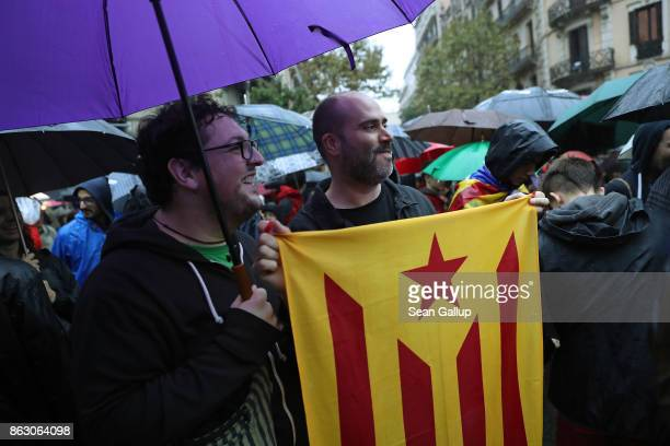 Protesters including one holding a Catalonian independence flag gather in pouring rain outside the building that houses the representation of the...