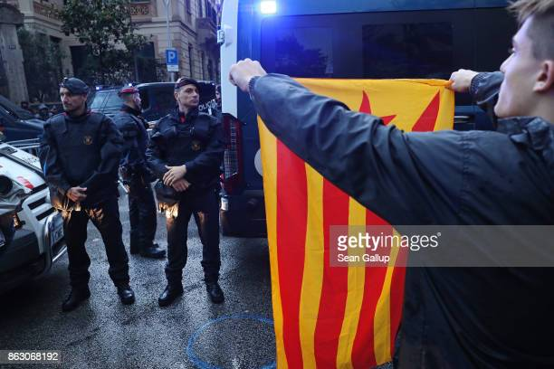 Protesters including one holding a Catalonian independence flag towards Catalonian riot police gather in between bouts of pouring rain outside the...
