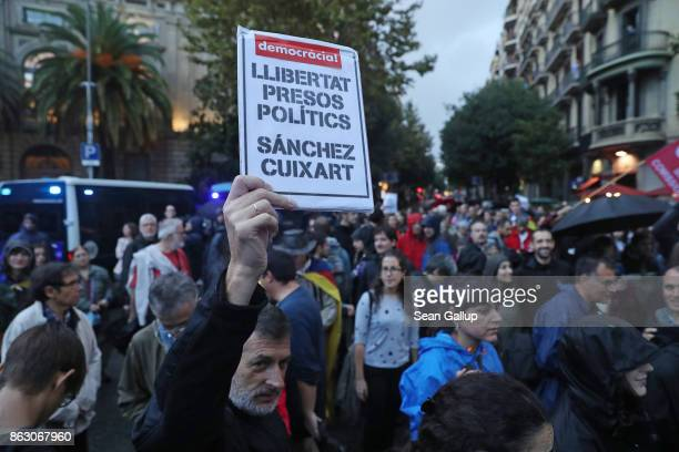 Protesters including one holding a sign demanding the release of Catalonian independence leaders Jordi Sanchez and Jordi Cuixart gather in between...