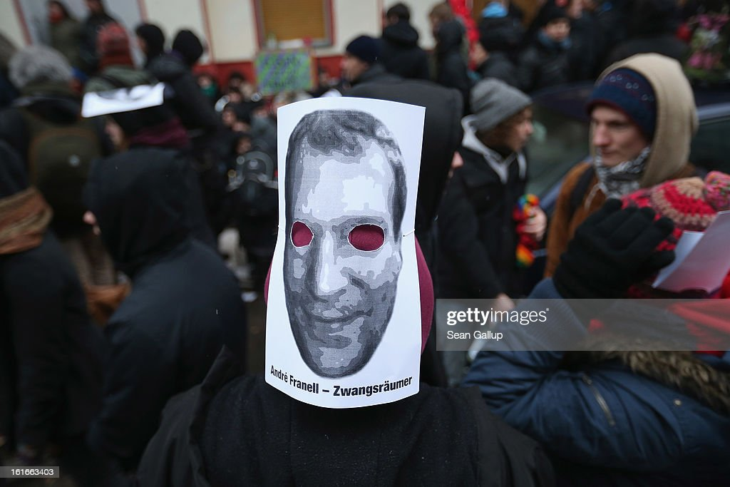Protesters, including one wearing a mask with a photo of landlord Andre Franell to demonstrate near the entrance to Lausitzer Strasse 8 to prevent the eviction of the German-Turkish Gulbol family as riot police look on on February 14, 2013 in Berlin, Germany. Several hundred protesters arrived to demonstrate in support of Ali Gulbol, his wife and two sons, who face eviction from their apartment in Kreuzberg district despite the fact that they invested EUR 20,000 into their apartment and have paid all their outstanding rent, albeit behind schedule. The case is highlighting an ongoing controversy over gentrification in parts of Berlin, where rising housing prices are luring investors and forcing long-standing tenants out.