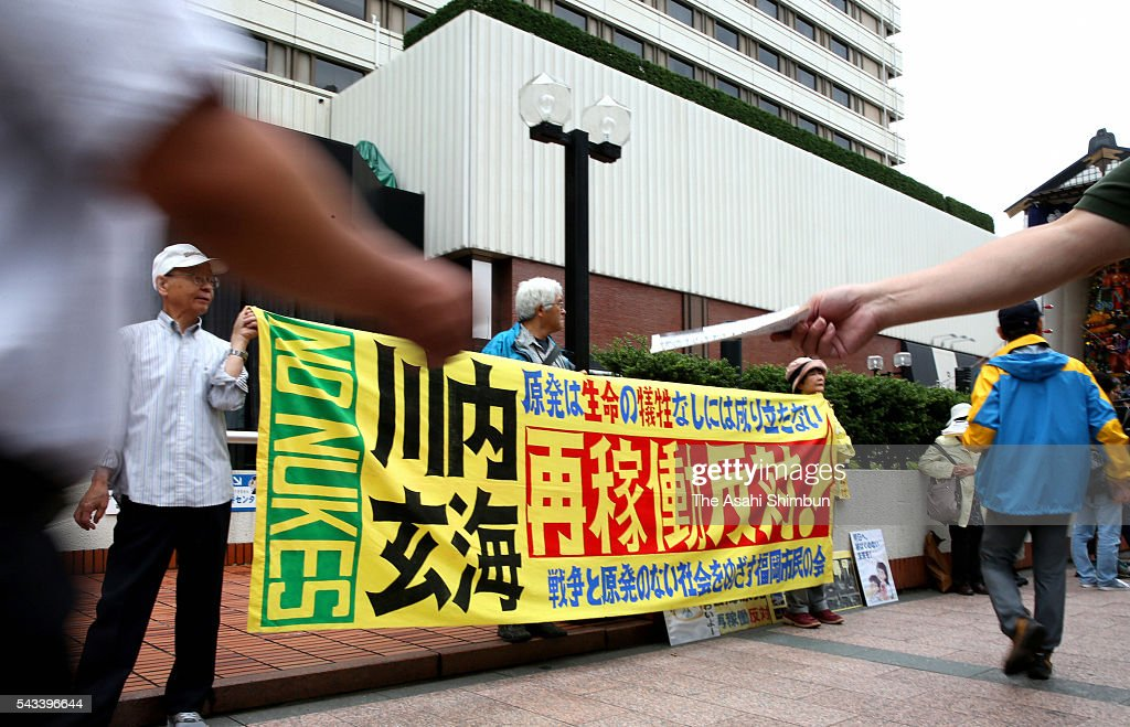 Protesters including shareholders hold up signs criticising Kyushu Electric Power Co. executives in front of the annual shareholders' meeting site on June 28, 2016 in Fukuoka, Japan. Japan's nine major electric power companies faced renewed calls to end their dependence on nuclear energy at their annual shareholders' meetings. However, as such proposals require approval by a two-thirds majority of shareholders with voting rights for passage, all were expected to be rejected.