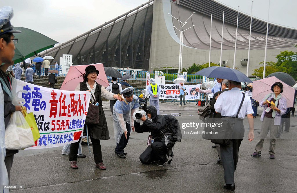 Protesters including shareholders hold up signs criticizing Tokyo Electric Power Co. executives in front of the Yoyogi First Gymnasium where the utility held its annual shareholders' meeting on June 28, 2016 in Tokyo, Japan. Japan's nine major electric power companies faced renewed calls to end their dependence on nuclear energy at their annual shareholders' meetings. However, as such proposals require approval by a two-thirds majority of shareholders with voting rights for passage, all were expected to be rejected.