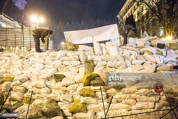 Protesters installing metal sheet barriers and barbed wire on a new reinforced barricade on Maidan Square on December 11 2013 in Kiev Ukraine...