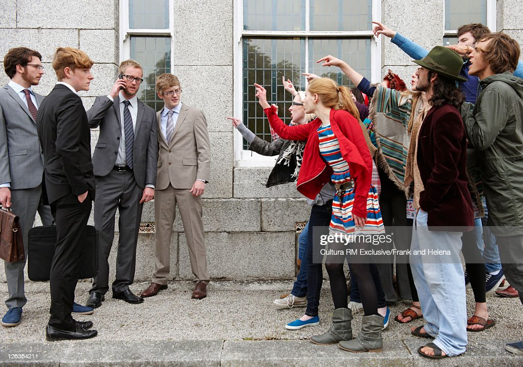 Protesters jeering businessmen : Stock Photo