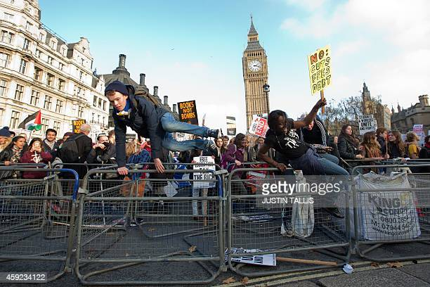 Protesters jump over the barrier to enter Parliament Square during a march against student university fees near the Houses of Parliament in central...