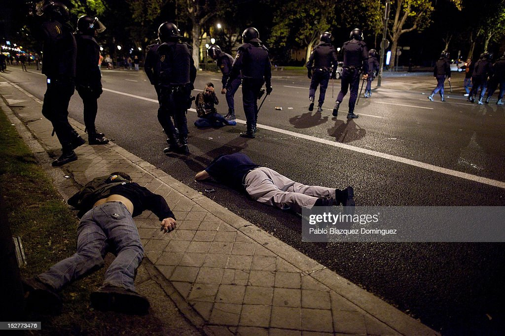 Protesters lay on the ground after riot police baton charged over them at Neptuno Square during demonstrations surrounding the Spanish Parliament on September 25, 2012 in Madrid, Spain. Demonstrators from various organizations, demanding a new constitutional process, are marching today from three different locations in the center of Madrid to the lower house in the Spanish parliament.