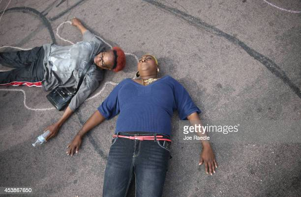 Protesters lay on the ground to draw lines around their bodies as they and other demonstrators protest outside of the Buzz Westfall Justice Center...