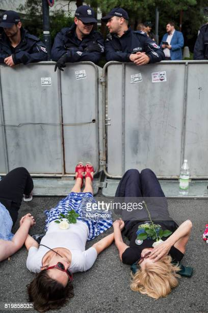 Protesters lie against a barrier guarded by Policemen in front of the Sejm building in Warsaw Poland on 20 July 2017 People protest against...