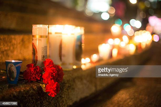 Protesters light candles at the Angel of Independence in Mexico City Mexico on October 11 2014 during a protest demanding the appearance of the 43...