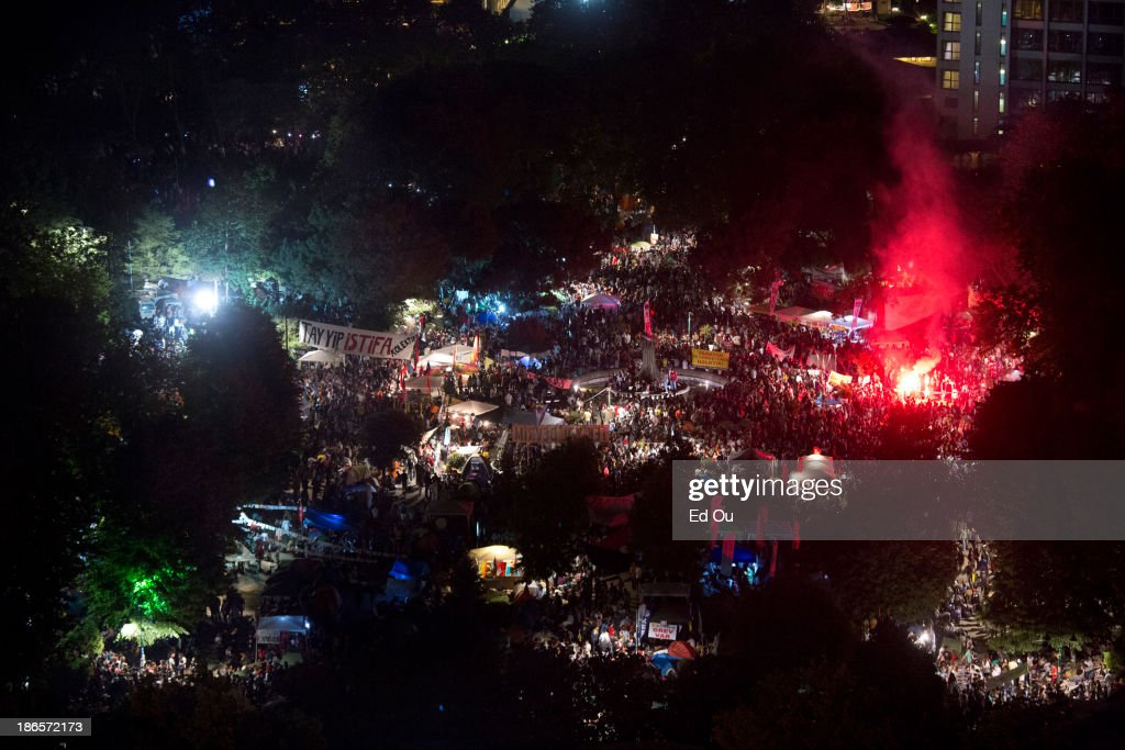 Protesters light red smoke flares during a mass protest and sitin of Gezi Park in Istanbul Turkey on June 9 2013 What started out as a protest over...