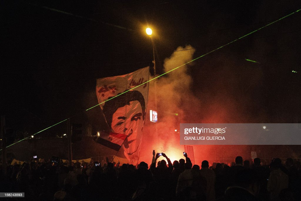 Protesters light up a flair as thousands of Egyptian opposition supporters rally outside of the Presidential palace to protest against the upcoming referendum on the new draft constitution on December 11, 2012, in Cairo. Egypt's powerful army has called for President Mohamed Morsi and the secular opposition to meet later in the day to stop a crisis over an imminent constitutional referendum from tearing the country apart. AFP PHOTO/GIANLUIGI GUERCIA