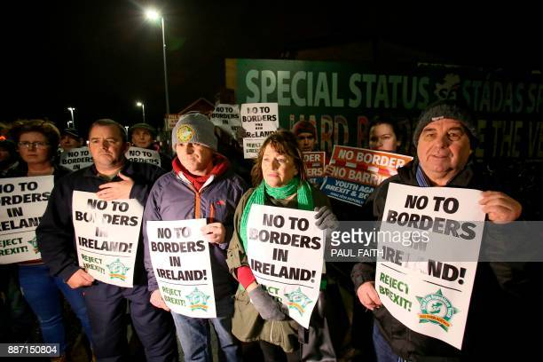 Protesters line a road holding placards near a new antiBrexit mural erected by Republican party Sinn Fein in west Belfast on December 6 2017 to call...