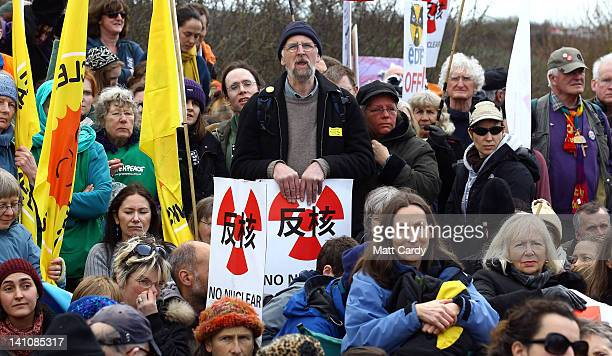 Protesters listen to speakers at the gates to the Hinkley Point nuclear power station as they gather to mark the first anniversary of the Fukushima...