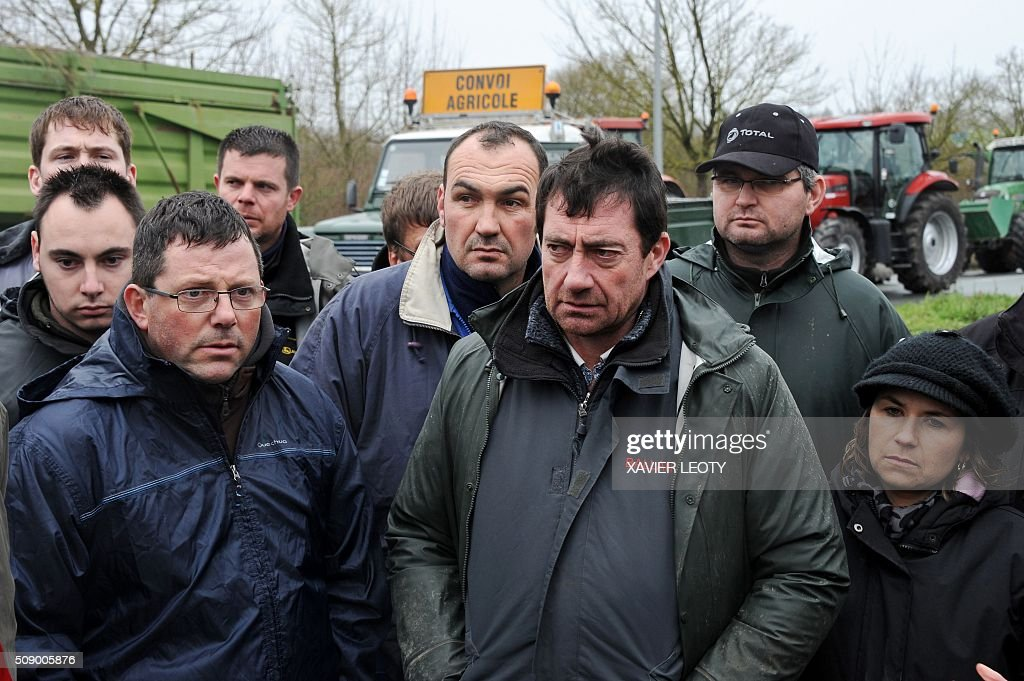 Protesters look on as they block a road near Saintes, western France, on February 8, 2016, during a demonstration by farmers against the purchase price of their products by supermarkets. Over 100 tractors were used by mostly pig and dairy farmers to block strategic points giving access to the city, disrupting traffic and closing an interchange of the A10 motorway. / AFP / XAVIER LEOTY