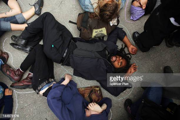 Protesters many affiliated with the Occupy Wall Street movement lay down while demonstrating in front of the Boeing headquarters on the second day of...