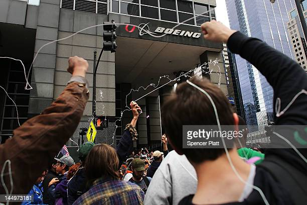 Protesters many affiliated with the Occupy Wall Street movement shoot aerosol string as they demonstrate in front of the Boeing headquarters on the...