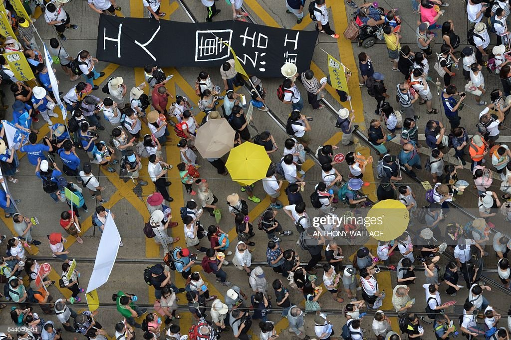 Protesters march along a road during a pro-democracy rally in Hong Kong on July 1, 2016, traditionally a day of protest which also marks the anniversary of the handover from Britain to China in 1997. Protesters took to the streets of Hong Kong on July 1 to mark the anniversary of the city's handover from Britain to China, with pro-independence groups rallying for the first time amid fears Beijing is tightening its grip. / AFP / ANTHONY
