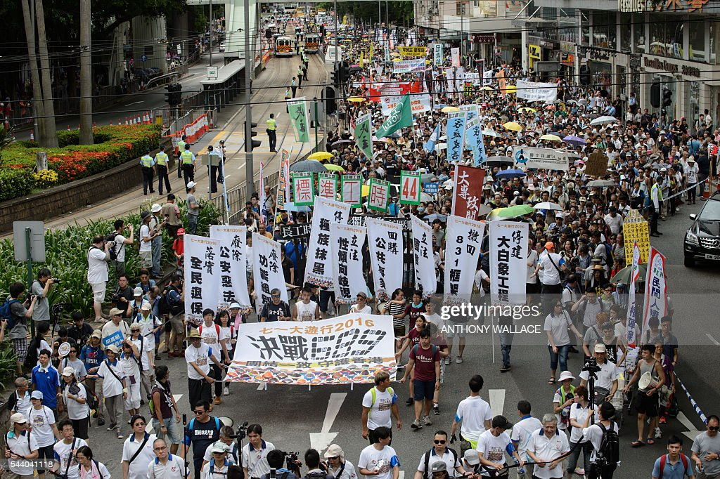 Protesters march along a road during a pro-democracy rally in Hong Kong on July 1, 2016, traditionally a day of protest which also marks the anniversary of the handover from Britain to China in 1997. Protesters took to the streets of Hong Kong on July 1 to mark the anniversary of the city's handover from Britain to China, with pro-independence groups rallying for the first time amid fears Beijing is tightening its grip. / AFP / Anthony Wallace
