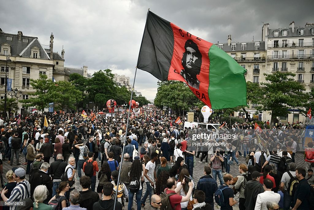 Protesters march as they wave a flag of revolutionary icon Ernesto 'Che' Guevara during a demonstration against controversial labour reforms, on June 28, 2016 in Paris. Thousands of people took to the streets of Paris today in the latest protest march in a marathon campaign against the French Socialist government's job market reforms. / AFP / PHILIPPE