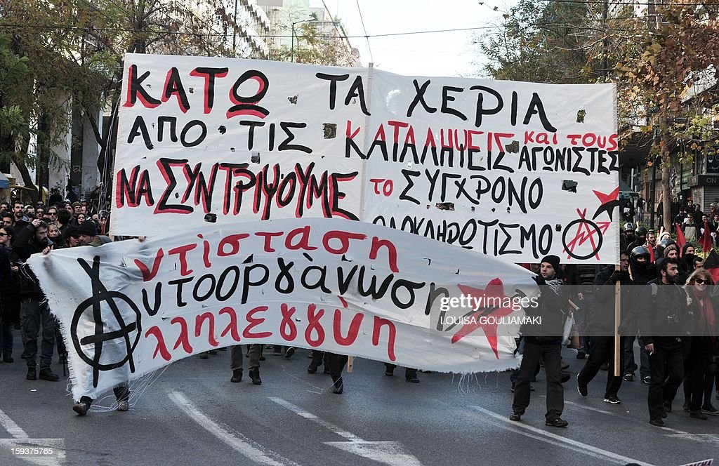 Protesters march behind a banner reading 'hands off the squats' in Athens on January 12, 2013. Several thousand people demonstrated in Athens to protest recent police operations against squatters in public buildings that have been condemned by the opposition. The protesters -- estimated by police at around 3,500 and nearly double that by media -- marched to the Athens court complex and police headquarters to demand the release of scores of individuals arrested in the sweeps. One of the central Athens buildings, a 19th-century former school, had been occupied for over two decades. The other is a stately block of flats whose former occupants include legendary soprano Maria Callas before her rise to fame. AFP PHOTO/ Louisa Gouliamaki