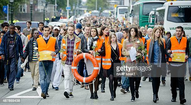 Protesters march during a silent rally in support of migrants and refugees in The Hague on September 12 2015 Thousands of Europeans were expected to...