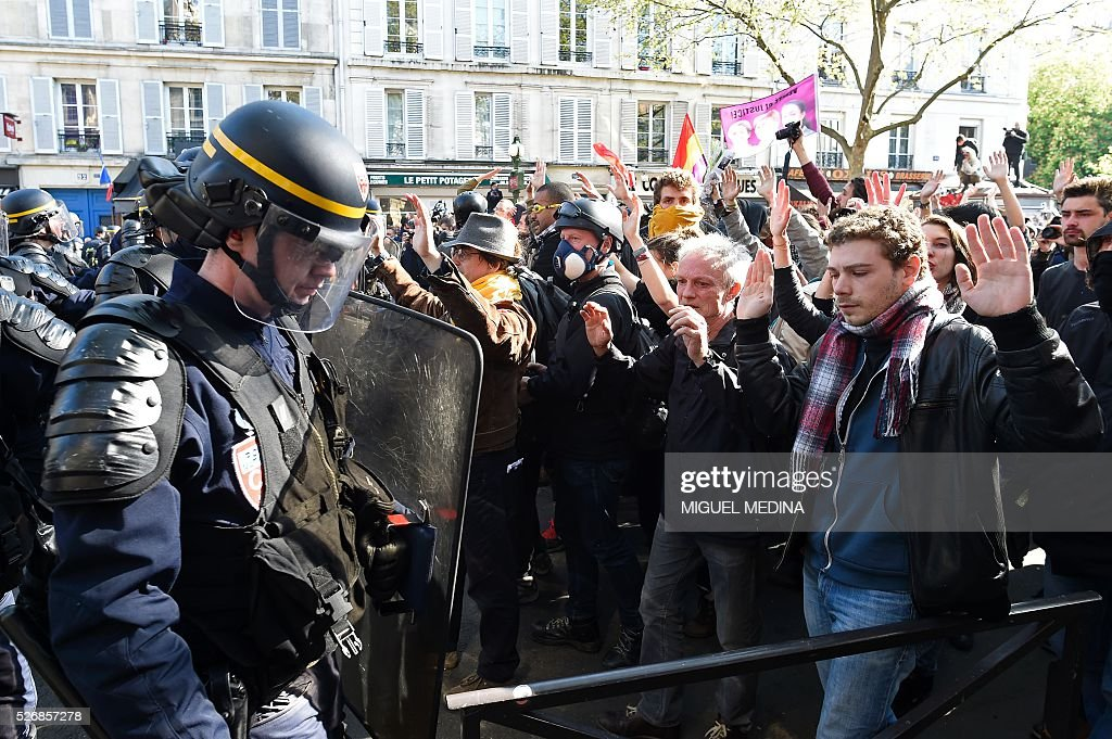 Protesters march facing riot police with their hands raised during a traditional May Day demonstration on May 1, 2016, in Paris.