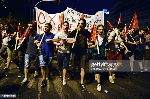 Protesters march holding banners and flags in front of the Greek parliament in Athens during an antiausterity protest on July 15 2015 Antiausterity...