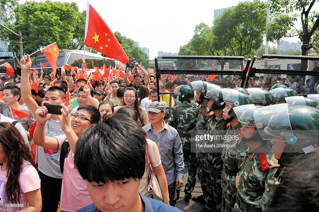 Protesters march on while paramilitary Police stand guard during an anti Japan rally at Japanese Consulate General on September 18, 2012 in Shanghai, China. There were protests in many major cities in China, including Shanghai, Shenzhen, Shenyang, Hangzhou, Harbin, Qingdao and Hong Kong as they oppose to the Japanese government's purchase of the disputed Senkaku/Diaoyu islands.