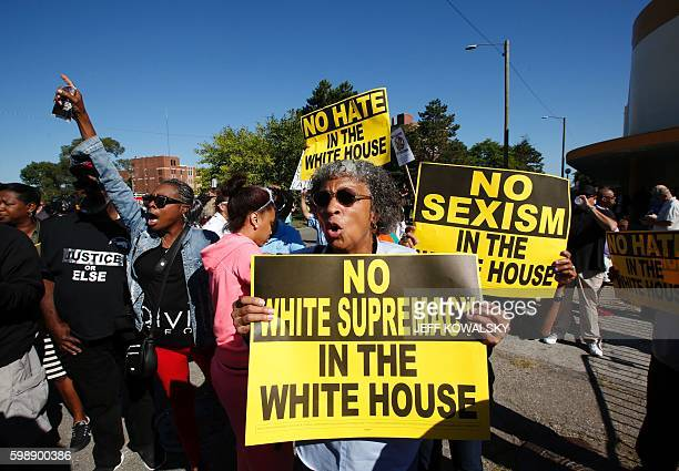 Protesters march outside of Great Faith Ministries Church in Detroit before a visit by US Republican Presidential candidate Donald Trump on September...