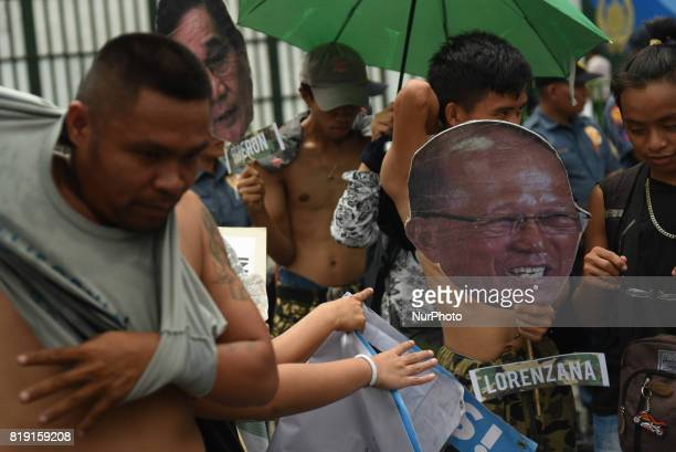 Protesters march towards the Department of National Defense gate in Quezon City north of Manila on 20 July 2017 The protesters holding print out...