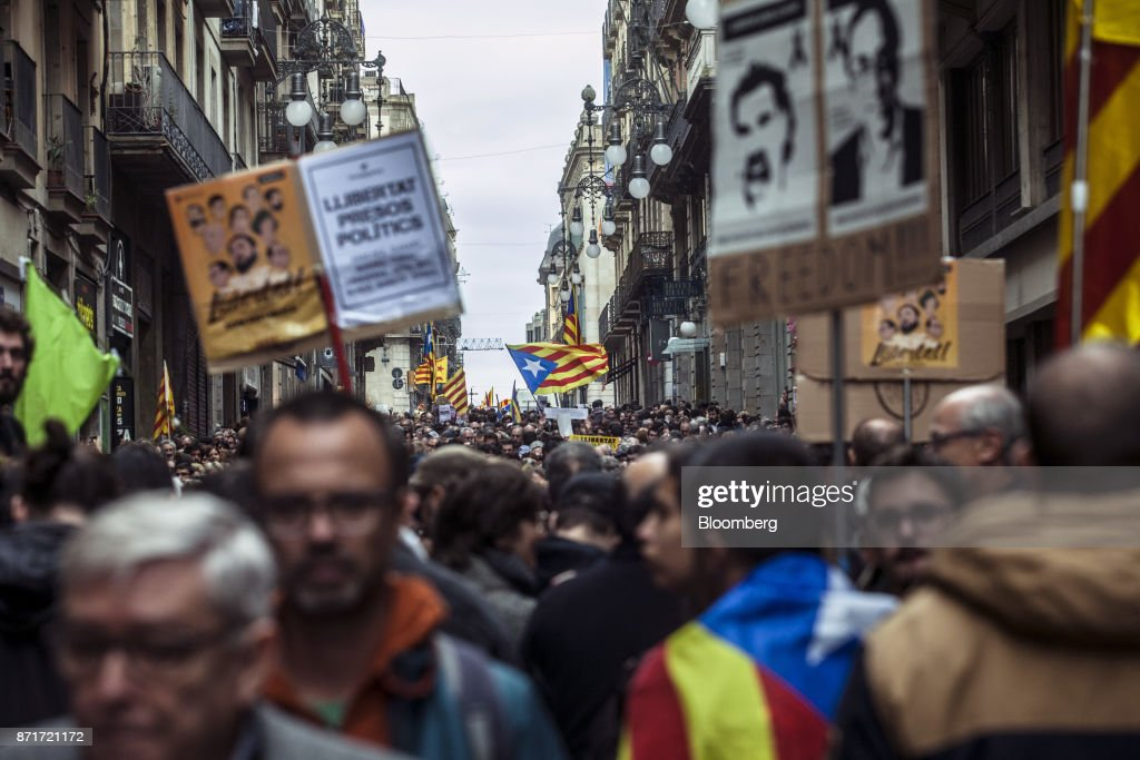Protesters march with photographs of Catalan activistsJordi Sanchez andJordiCuixartand call for 'Freedom for political prisoners' during a regional strike called by pro-independence union in Barcelona, Spain, on Wednesday, Nov. 8, 2017. Spanish Prime MinisterMariano Rajoyinvoked extraordinary powers last month to reassert his authority over Catalonia and fire Catalan presidentCarles Puigdemont and his government.Photographer: Angel Garcia/Bloomberg via Getty Images