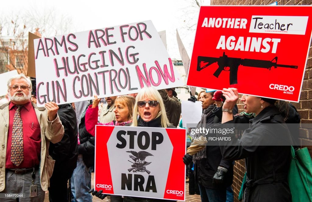 Protesters marching with the social activist group CREDO along with other concerned citizens descend on the offices of the NRA's (National Rifle Association)Capitol Hill lobbiest's office demanding the pro-gun lobby stand down in reaction to the shooting at Sandy Hook Elementary School December 17, 2012, in Washington, DC. A leading Democratic senator launched a bid Sunday to ban assault weapons in the wake of the latest deadly US school shooting, announcing that she will put a bill before Congress on January 3.Dianne Feinstein, the influential chair of the Senate Intelligence Committee, said she believed President Barack Obama would support her legislation, also aimed at outlawing magazines carrying more than 10 bullets. AFP Photo/Paul J. Richards