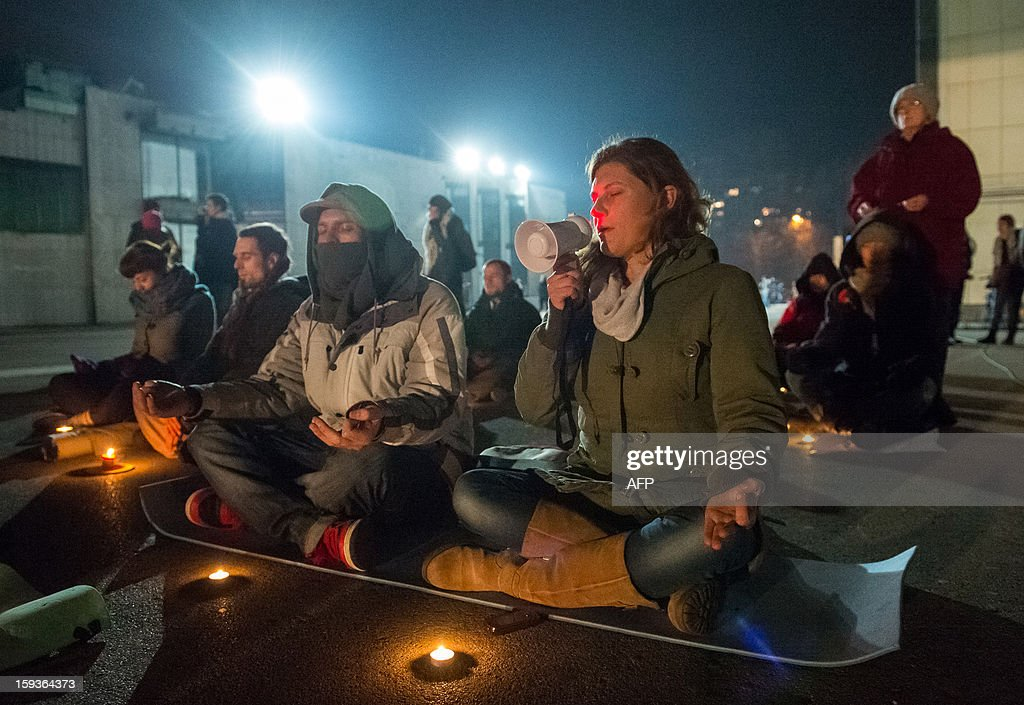 Protesters meditate during a demonstration against political corruption and the Prime Minister in Ljubljana, on January 11, 2013. Several thousand people in Slovenia's capital today joined in one of the biggest anti-government rallies in recent months, demanding the resignation of Prime Minister Janez Jansa, who has been accused of corruption. State radio estimated over 10,000 people took part in the protest called by civil groups under the slogan 'For the government's resignation and the renewal of Slovenia.' Police put the figure closer to 8,000. AFP PHOTO / Jure Makovec