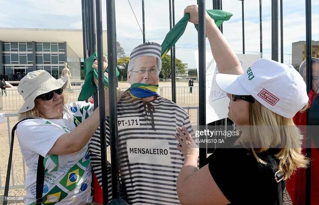 Protesters mock to hang a dummy representing Jose Dirceu, former Chief of Staff of President Luiz Inacio Lula da Silva, one of the accused in the Mensalao scandal, during a protest against the approval of the review of the appeals that will result in a new trial for 11 of the accused in the Mensalão scandal, in Brasilia on September 18, 2013. The session was held to review the appeals of those convicted for diverting at least $35 million in public money to bribe legislators to get their support for former President Luiz Inacio Lula da Silva's minority government after he took office in 2003. AFP PHOTO/Evaristo Sa
