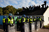 Protesters on the roof look down on lines of riot police Travellers at Dale Farm site prior to eviction Riot police and bailiffs were present on 20th...