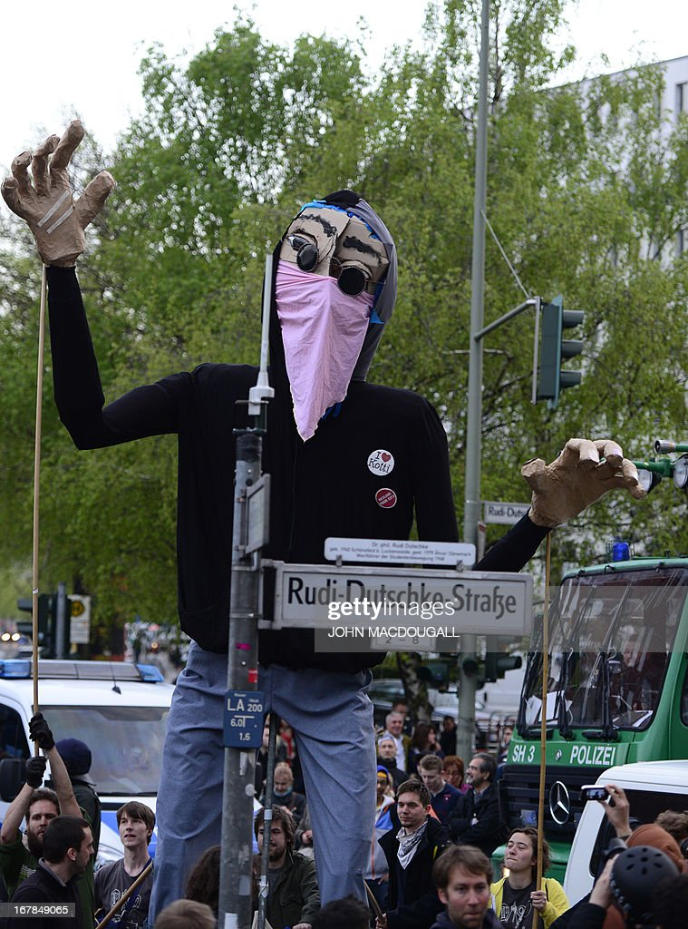 Protesters operate a giant puppet dressed as a demonstrant behind a street sign named after Rudi Dutschke, a leading person during the German student movement in the 60s, during the 'Revolutionary' May Day demonstration on May 1, 2013 in Berlin. Thousands of leftists, trade unionists and workers took to the streets of the capital on the occasion of International labour day.