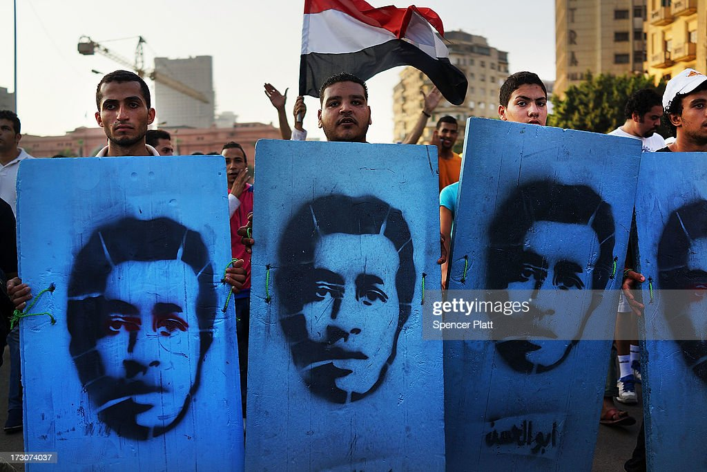 Protesters opposed to ousted Egyptian President Mohamed Morsi enter Tahrir Square carrying placards representing people killed during demonstrations...