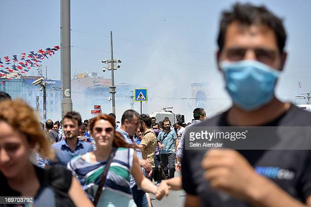 Protesters opposed to the construction of a shopping mall react as tear gas is fired by police in Taksim Park one of the last green spots in the city...