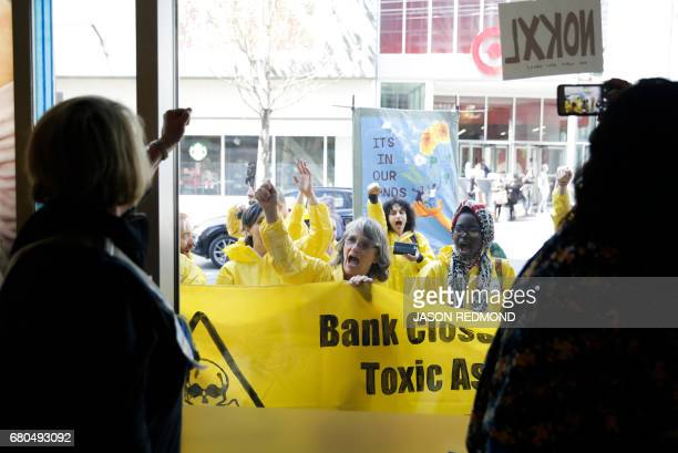 Protesters outside cheer on indigenous leaders and climate activists inside a Chase Bank branch as they disrupt business to protest tar sands...