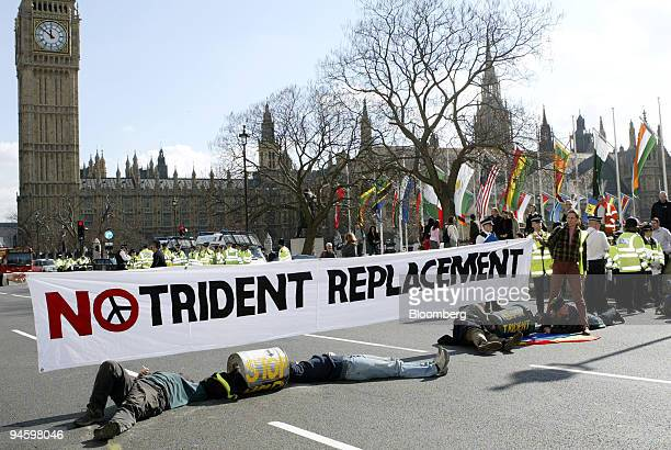 Protesters outside parliament chain themselves to metal barrels and obstruct traffic during protests against the Trident vote in London UK Wednesday...