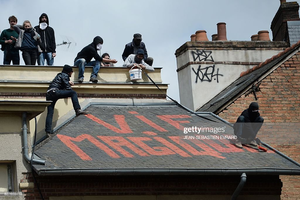 Protesters paint a message reading 'magical life' on the roof of the People's house on May 3, 2016 in Rennes, western France, during a protest against the government's planned labour law reforms. High school pupils and workers protest against deeply unpopular labour reforms that have divided the Socialist government and raised hackles in a country accustomed to iron-clad job security. / AFP / JEAN