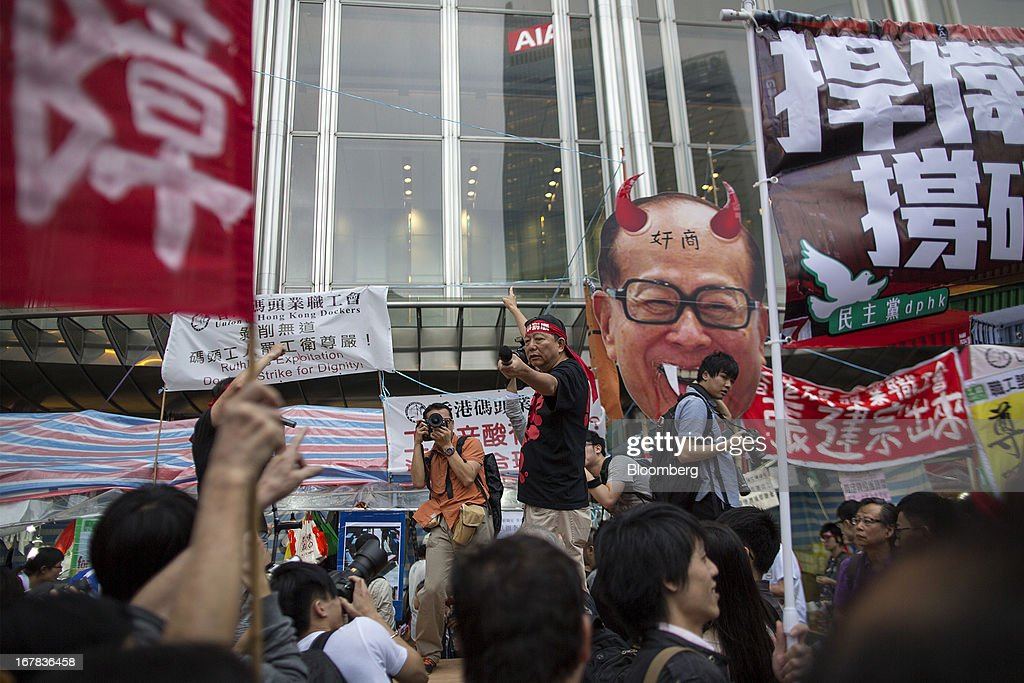 Protesters pass by an effigy of billionaire Li Ka-shing, chairman of Hutchison Whampoa Ltd. and Cheung Kong (Holdings) Ltd., as Lee Cheuk-yan, Legislative Council member and general secretary of the Hong Kong Confederation of Trade Unions, center, holds a microphone outside the Cheung Kong Center during a Labor Day march in Hong Kong, China, on Wednesday, May 1, 2013. Thousands of Hong Kong residents took to the streets today for Labor Day marches to petition for better labor conditions and in support of strike action by workers at docks operated by Li. Photographer: Jerome Favre/Bloomberg via Getty Images
